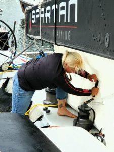 Diane grinds a halyard to get Ryan partway up the mast.